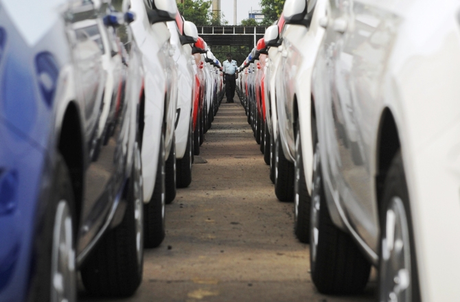 An employee walks between parked Hyundai cars ready for shipment at a port in Chennai.