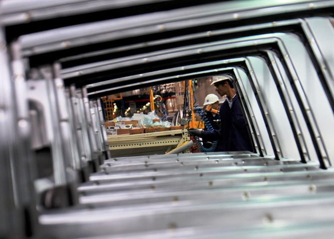 Employees are seen working through the doors of Chevrolet Beat cars on an assembly line at the General Motors plant in Talegaon.