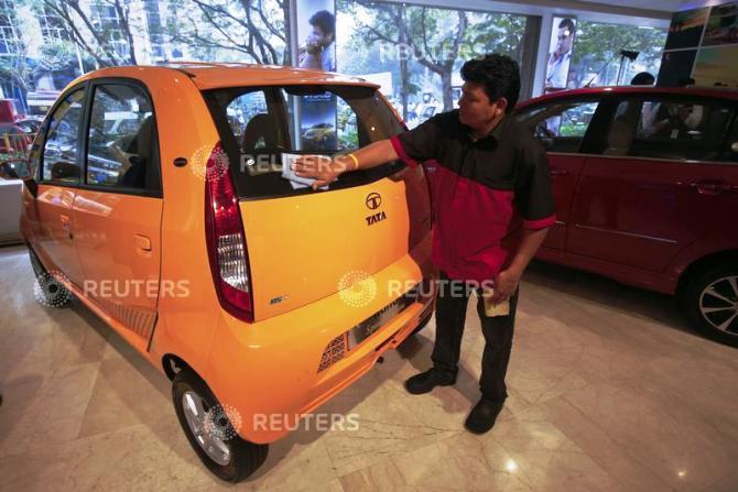 A showroom attendant cleans a Tata Nano car at the flagship Tata Motors showroom.