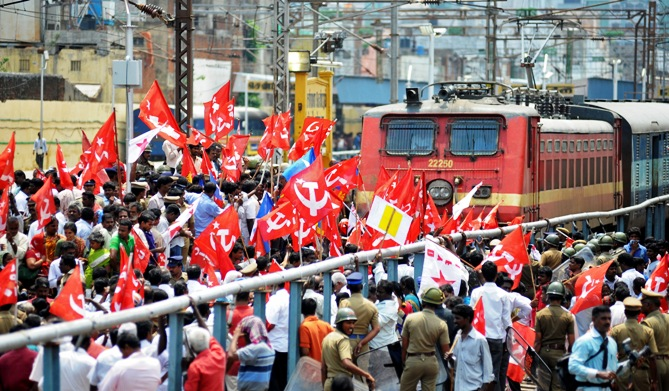 Activists of the Communist Party of India-Marxist (CPI-M) block a passenger train while protesting during a nationwide strike in Chennai.