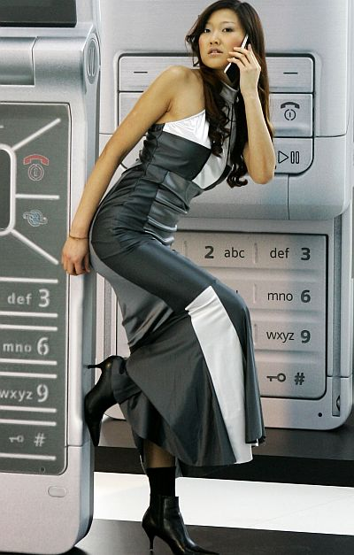 A model poses in front of mock-up mobile phones.