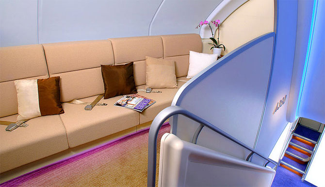 A view of a social area and stair case on board the A380.