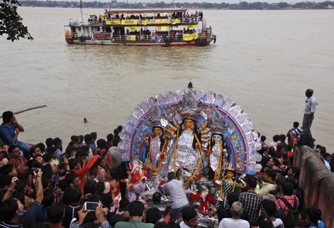 Devotees prepare to immerse an idol of goddess Durga in the waters of river Ganges on the last day of the Durga Puja festival in Kolkata.