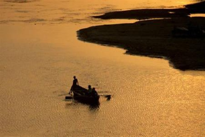 A man rows his boat in the waters of river Ganga during the sunset in Allahabad.