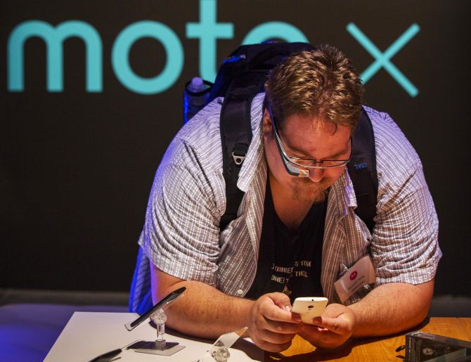 A man using Google Glass examines one of Motorola's new Moto X phones at a launch event in New York.