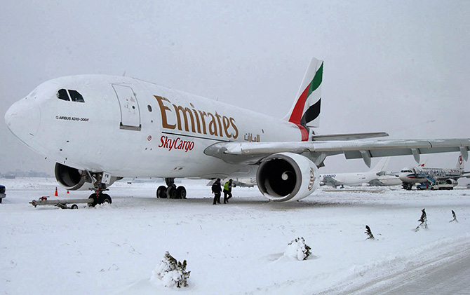 Airport officials walk under an Emirates A310 Airbus cargo plane in the snow at Ataturk Airport in Istanbul.