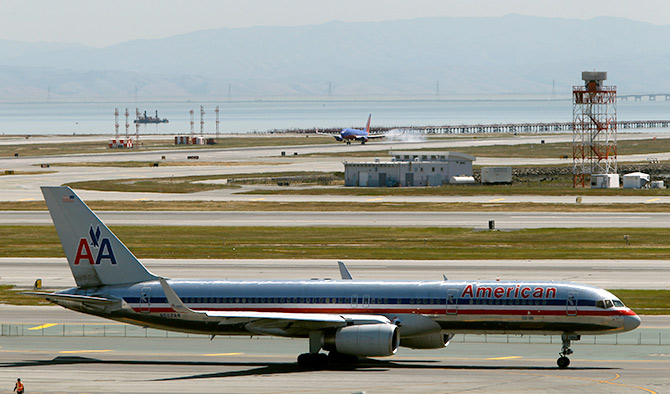 An American Airlines passenger jet taxis to a runway as a Southwest Airlines jet (rear) lands at San Francisco International Airport.