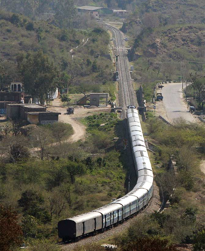 A passenger train moves along the Jammu-Udhampur rail line.