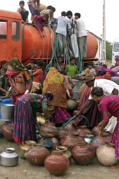 Indian tribal women fill drinking water in their p
