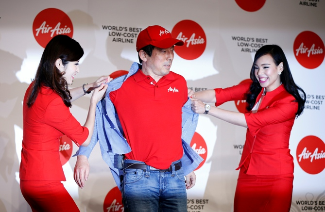 AirAsia flight crew members take off AirAsia Japan CEO Yoshinori Odagiri's (C) shirt to show the company's uniform underneath during an AirAsia Group news conference in Tokyo July 1, 2014.
