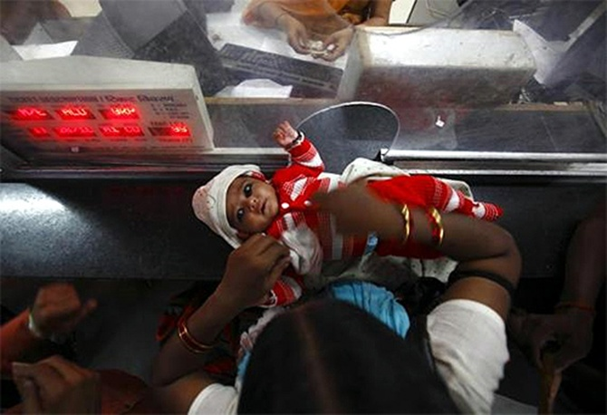 A woman keeps her child on the ticket counter as she buys a train ticket.