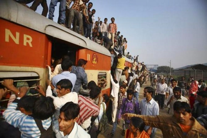 Commuters struggle to board a train at Noli railway station in Uttar Pradesh.