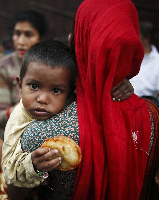 A woman carries a child as she begs for money.