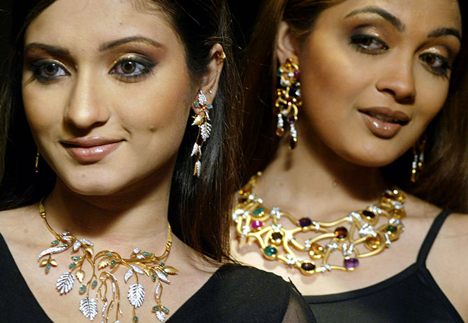Indian models pose with gold and precious stones combined ornaments during a fashion show by Indian student designers in Kolkata.