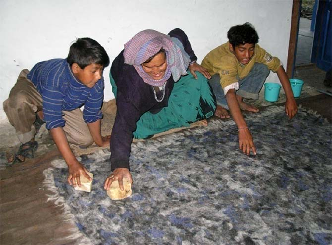 Villagers make woollen felt from wool.