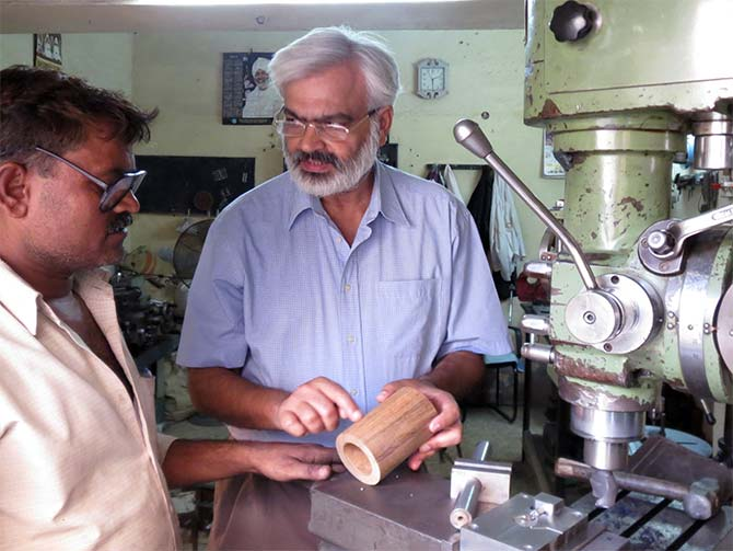 Yogeshwar Kumar instructing a technician on fabrication of equipment for power house. He has been designing power station and gets equipment fabricated in small units in Delhi