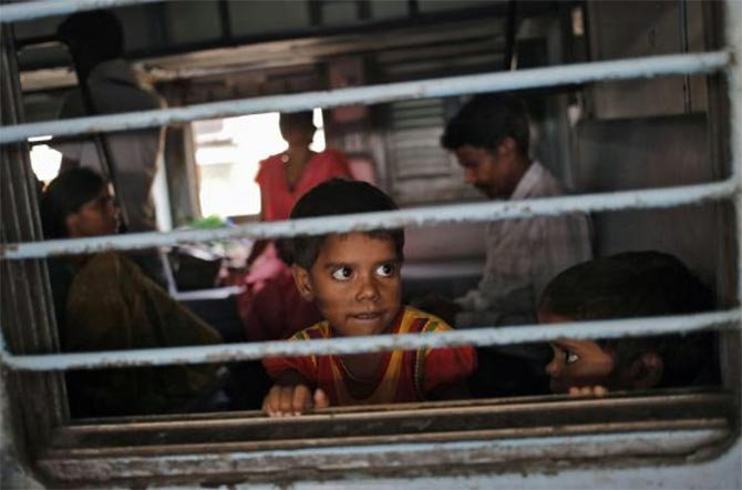 A girl looks out through the window of a passenger train at a railway station in New Delhi.