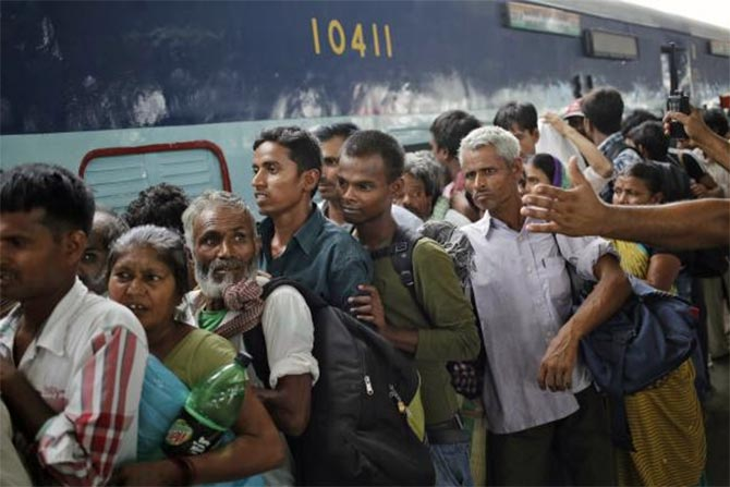 Passengers stand in a queue to board a train at a railway station in New Delhi.