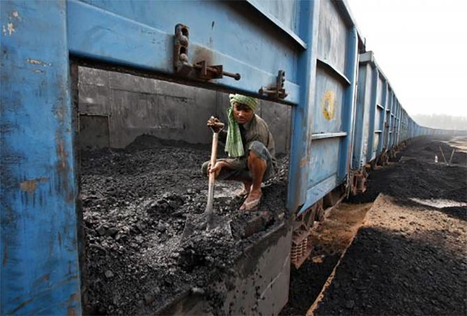 A worker unloads coal from a goods train at a railway yard in Chandigarh.