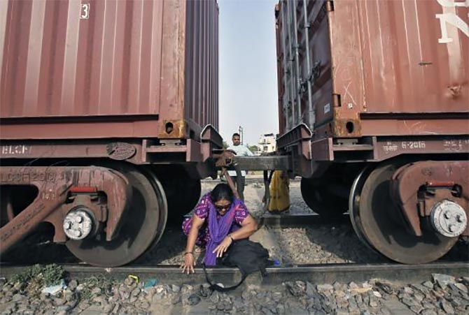 A woman crosses under the carriages of a parked goods train at Loni town in Uttar Pradesh.