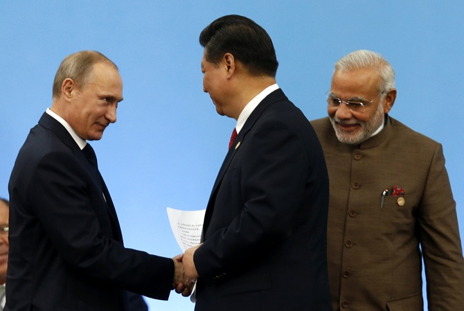 Russia's President Vladimir Putin (L) shakes hands with China's President Xi Jinping as India's Prime Minister Narendra Modi (R) looks on during the VI BRICS Summit in Fortaleza.