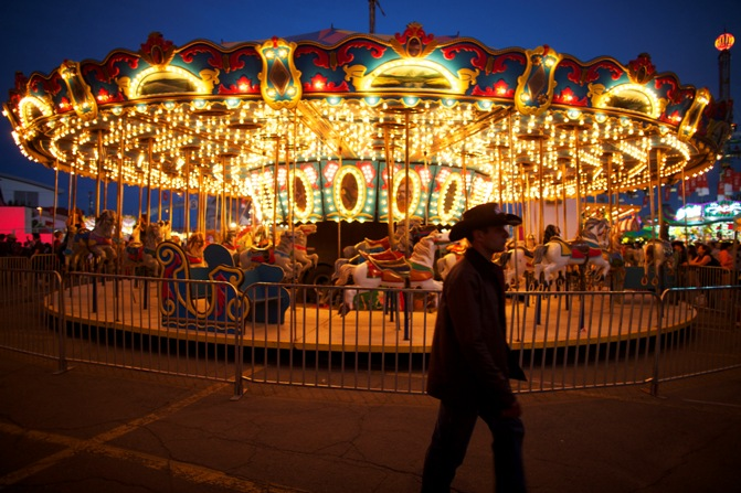 A cowboy walks by a carnival ride during day two of the Calgary Stampede in Calgar.