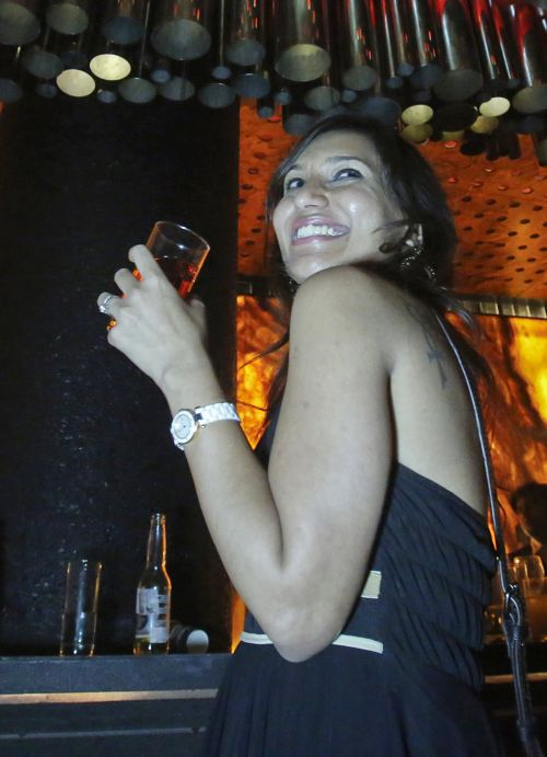 A girl has a drink while standing next to the bar at the Ren by China Garden nightclub in Mumbai.