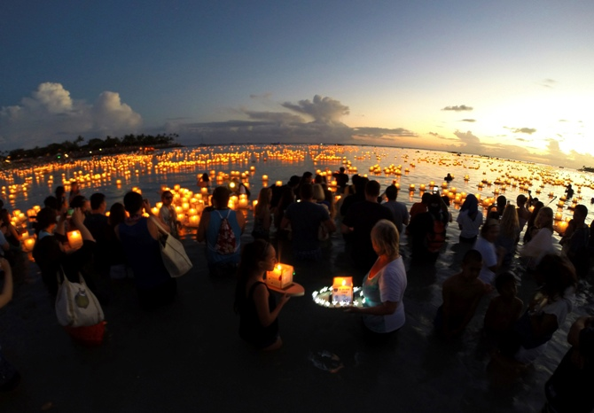 A large crowd gathers to release and watch floating lanterns on the water after being released during a ceremony marking remembrance and reflection, held by Shinnyo-en Buddhists honoring victims of war, famine, and natural disasters on Memorial Day, at Ala Moana Beach Park in Honolulu.