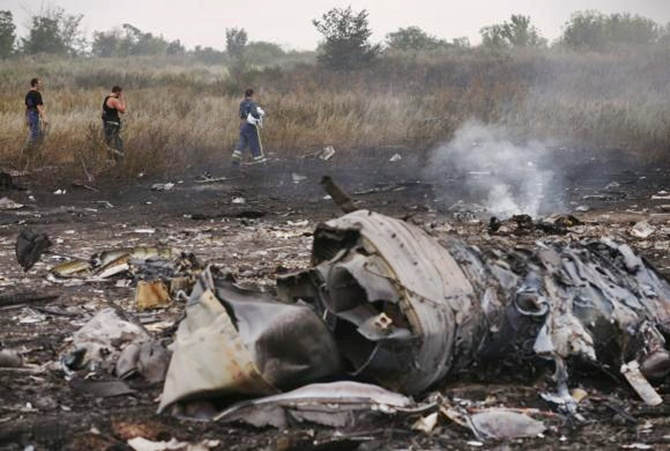 Emergencies Ministry members walk at the site of a Malaysia Airlines Boeing 777 plane crash near the settlement of Grabovo in the Donetsk region.