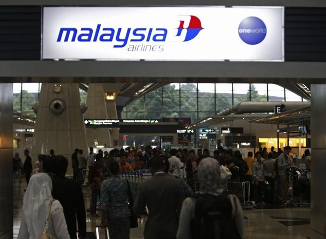 Passengers queue up at the Malaysia Airlines ticketing booth at the Kuala Lumpur International Airport in Sepang.