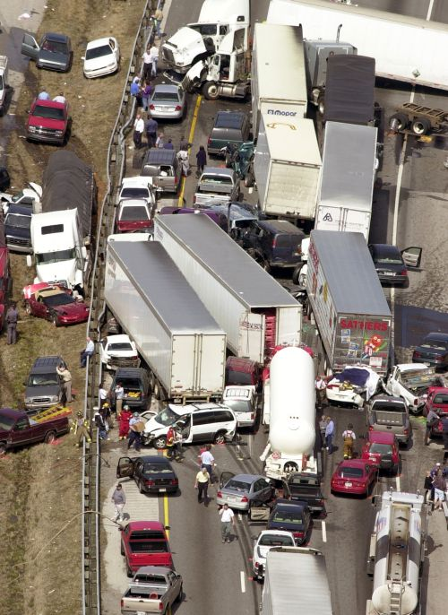 Dozens of vehicles sit on a highway after a deadly pileup along a foggy stretch of road.