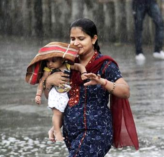 A woman carries her child through a heavy rain shower in Chandigarh.