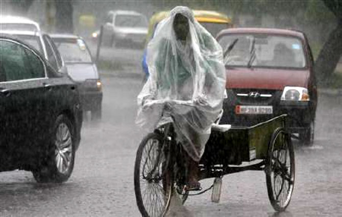 A man uses a plastic sheet to guard against a downpour while riding his trishaw in Chandigarh.