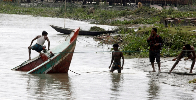 Workers try to retrieve a boat which sank in the Kirtankhola river during the storm at Barisal, 280km (174 miles) southwest of Dhaka.