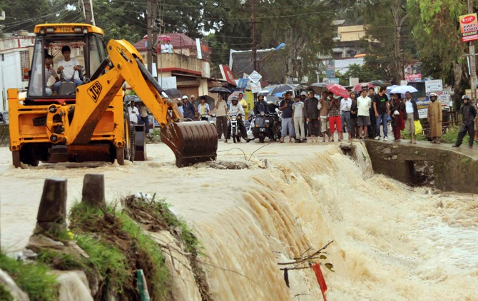 A bulldozer removes waste floating on a flooded street in Dehradun.