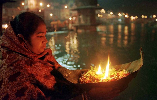 A woman prays with her offering to the Ganges river in Haridwar.