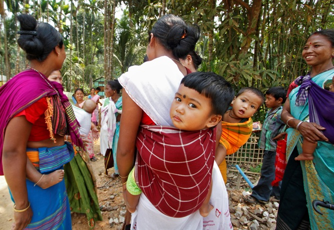 Women carrying their children stand after casting their vote at a polling station at Amguri village in Assam.