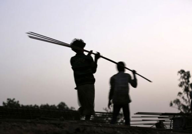 Labourers carry iron rods at the construction site of a flyover on the outskirts of Ahmedabad.