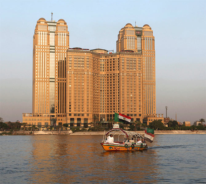 A small cruise boat passes Nile City Towers, which is owned by Naguib Sawiris the owner of Orascom Telecom, overlooking the river Nile in Cairo.