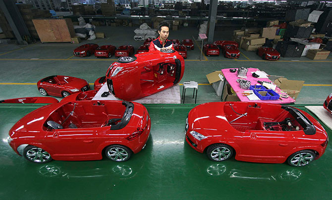A worker assembles toy cars at a production line inside a factory in Jinjiang, Fujian province, China.
