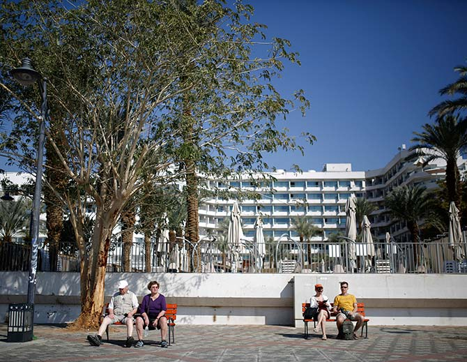People rest on benches outside a hotel in the Red Sea resort city of Eilat, one of Israel's most popular holiday spots.