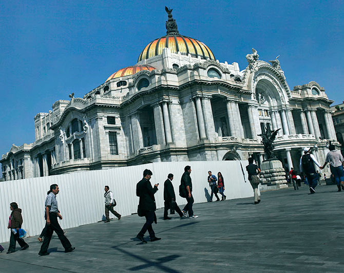 People walk in front of the Palace of Fine Arts in Mexico City.