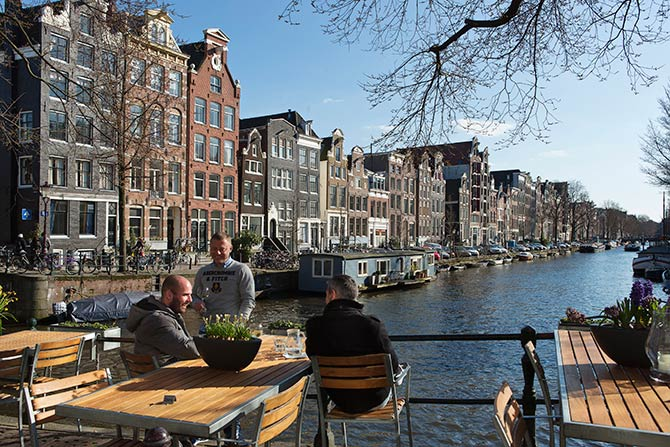 Men enjoy the afternoon sun at the Brouwersgracht canal in Amsterdam.