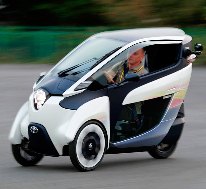 A journalist drives a Toyota ultra-compact, tandem two-seater electric vehicle i-ROAD during the Toyota Advanced Technologies media briefing in Tokyo.