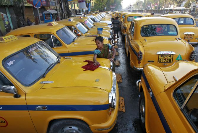 Sumitra Sarkar, 35, cleans a yellow ambassador taxi at a parking area along a roadside in Kolkata.