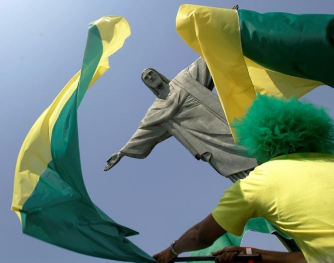 This file photograph shows a fan waving a flag in front of the Christ the Redeemer statue in Rio de Janeiro.