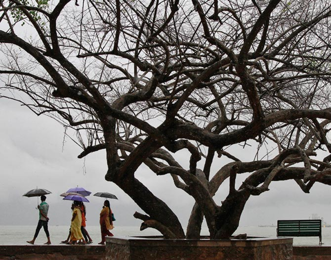 Beachgoers stroll along the Fort Kochi beach while holding umbrellas during a rain shower in Kochi.