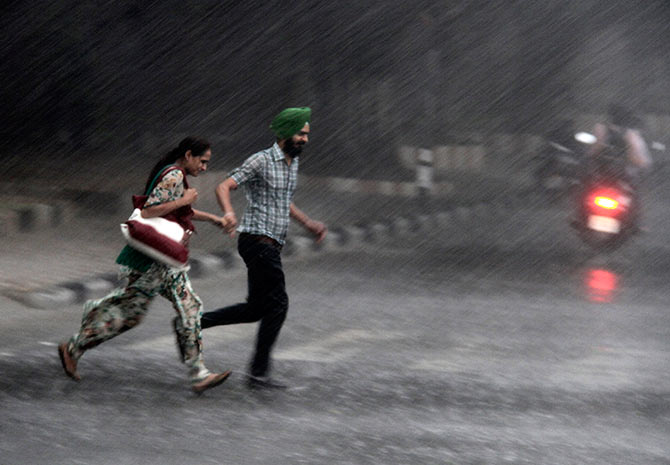 Commuters run for cover as they cross a road during monsoon rains in Chandigarh.