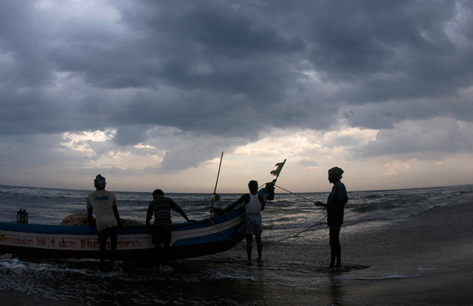 Indian fishermen stand with their boat against the backdrop of monsoon clouds on the marina beach in Chennai.