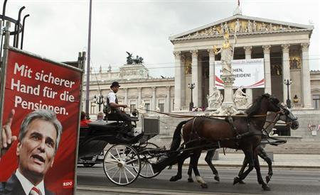 A traditional Fiaker carriage passes an election poster of Austrian Chancellor Werner Faymann of the social democrats (SPOe) in front of the parliament in Vienna September 4, 2013.